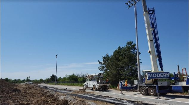 Soccer field floodlights being installed